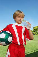 Boy (7-9 years) soccer player holding ball and water bottle, portrait
