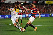 01.01.2014 Sydney, Australia. Wellingtons defender Ben Sigmund and Wanderers forward Mark Bridge in action during the Hyundai A League game between Western Sydney Wanderers FC and Wellington Phoenix FC from the Pirtek Stadium, Parramatta. Wellington won 3-1.
