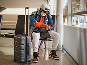 "17 MARCH 2020 - DES MOINES, IOWA:  PATRICK AWO, from Des Moines, cleans his hands with sanitizer after flying into Des Moines International Airport Tuesday. The airport was almost empty as air travel is greatly reduced because of the Coronavirus outbreak. Sunday night, the Governor of Iowa announced that the state health department had recorded ""community spread"" in Des Moines. Tuesday, the Governor ordered all restaurants and bars to close or transition to take out only. The Iowa Department of Public Health has urged all public buildings, like libraries and schools, to close, and all schools in Iowa are closed for at least 30 days.    PHOTO BY JACK KURTZ"