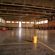 An empty hangar after the 'Red Arrows', Britain's Royal Air Force aerobatic team, have left their UK base at RAF Scampton for the sunnier climate and clearer skies of the Mediterranean at RAF Akrotiri in Cyprus. A lone engineer, left behind to continue the preparations before the start of the Summer air show season walks in the gap of the giant hangar doors. A yellow dustbin that collects foreign objects (FOD) is in the middle of the floor. The team will spend six weeks in Cyprus refining their air display techniques and skills before performing in front of the public from May onwards. Since 1965 they have flown over 4,000 such shows in 52 countries. The hangar dates to World War 2, housing Lancaster bombers of 617 Dambusters squadron who attacked the damns of the German Ruhr valley on 16th May 1943 using the Bouncing Bomb. This version of BAE Systems Hawks are low-tech, without computers nor fly-by-wire technology, Some of the team's aircraft are 25 years old and their airframes require frequent overhauls due.