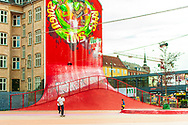 A skateboarder is pictured against a large red mural at Nørrebro's Superkilen outdoor area