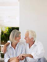 Senior couple sitting on verandah looking in eyes and smiling