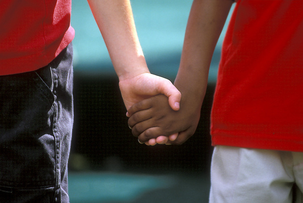 Stock photo of a close up of African American boy and caucasian boy holding hands