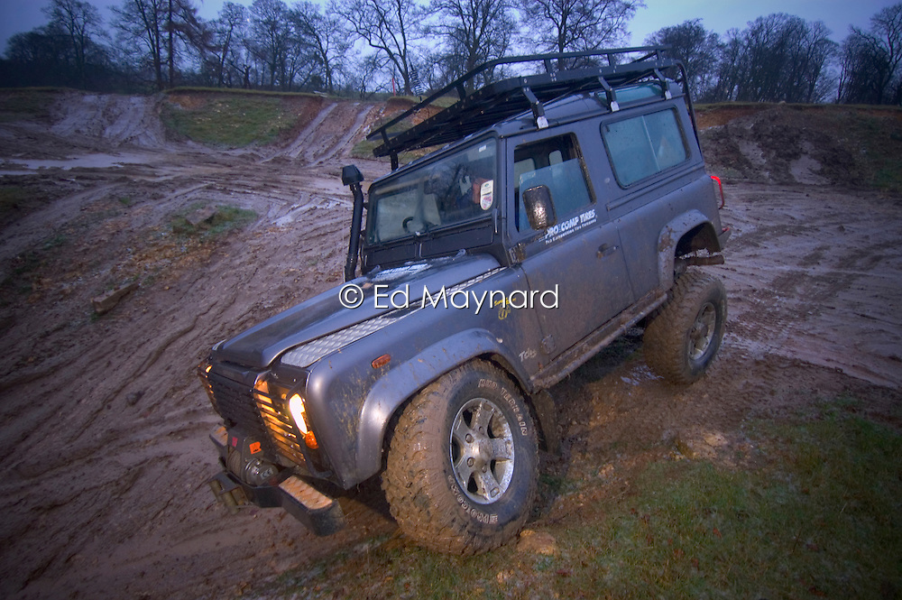 Land Rover Defender 90 traversing muddy ground, England, United Kingdom.