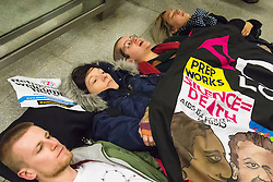"""St Pancras, London, January 16th 2016. Dozens of protesters hold an """"emergency demonstration and die-in"""" as France prepares to bulldoze the Jungle Camp at Calais. PICTURED: Protesters lie on the ground as part of their die-in at the entrance to the Eurostar terminal from the London Underground. ///FOR LICENCING CONTACT: paul@pauldaveycreative.co.uk TEL:+44 (0) 7966 016 296 or +44 (0) 20 8969 6875. ©2016 Paul R Davey. All rights reserved."""