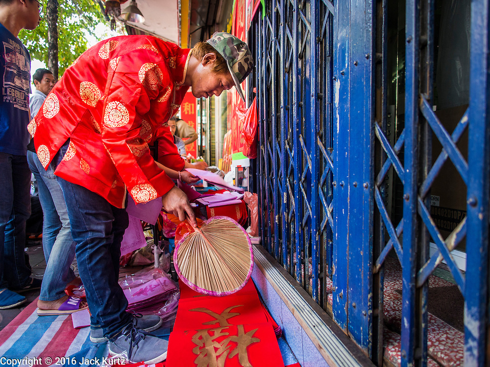 """04 FEBRUARY 2016 - BANGKOK, THAILAND: A worker dries freshly painted Chinese New Year calligraphy on a sidewalk in Bangkok's Chinatown district, before the celebration of the Lunar New Year. Chinese New Year, also called Lunar New Year or Tet (in Vietnamese communities) starts Monday February 8. The coming year will be the """"Year of the Monkey."""" Thailand has the largest overseas Chinese population in the world; about 14 percent of Thais are of Chinese ancestry and some Chinese holidays, especially Chinese New Year, are widely celebrated in Thailand.      PHOTO BY JACK KURTZ"""