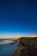 The stars of Orion and Canis Major (including Sirius) setting head first into the west over the sea stack formations of the Twelve Apostles on the Great Ocean Road, Victoria, Australia, with the stacks beginning to be lit by light from the rising nearly Full Moon behind the camera in the east. The sky is blue with moonlight. This was April 12, 2017.<br /> <br /> This is a stack of 8 x 15-second exposures, mean combined, for the ground to smooth noise, and one 15-second exposure for the sky, all at f/2.5 with the 14mm Rokinon lens at Canon 6D at ISO 800.