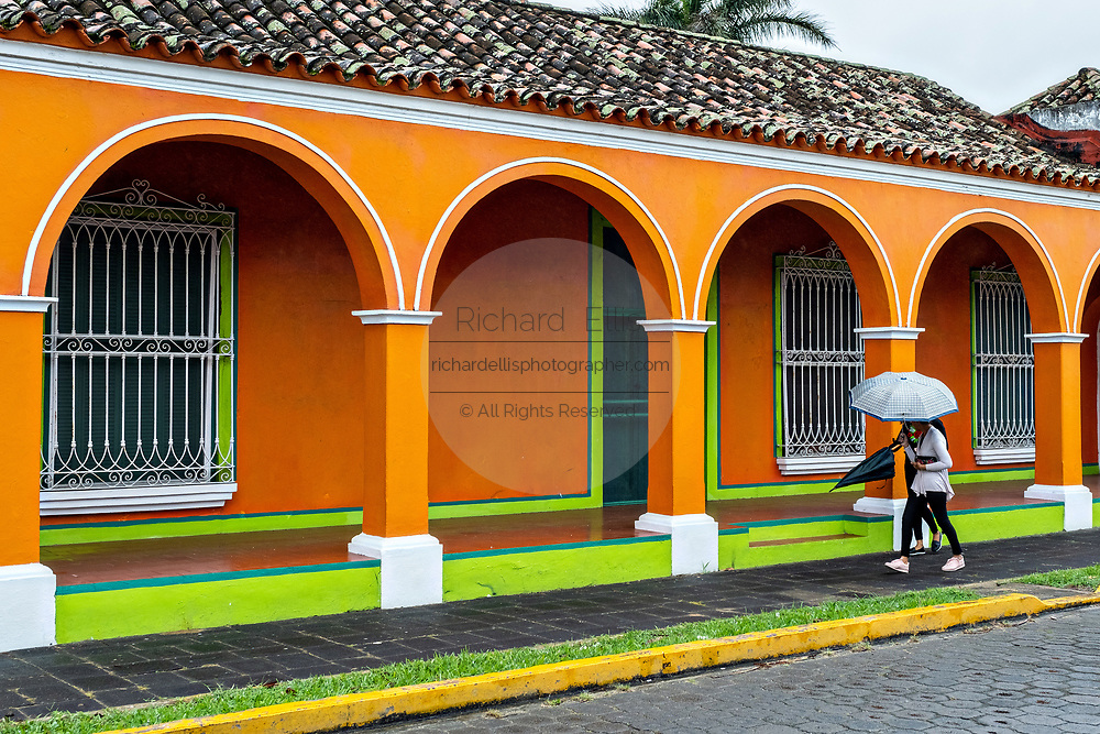 A woman walks with an umbrella past a brightly painted colonnaded style home in Tlacotalpan, Veracruz, Mexico. The tiny town is painted a riot of colors and features well preserved colonial Caribbean architectural style dating from the mid-16th-century.