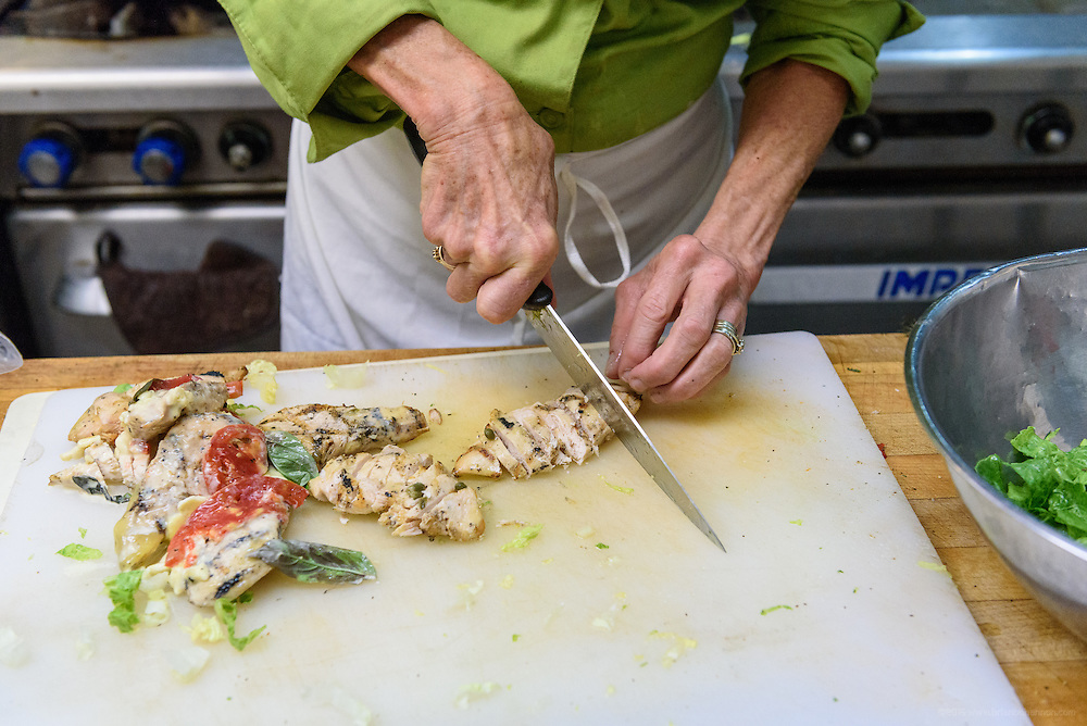 Chef Kathy Cary chops grilled chicken for a dish in the La Peche gourmet-to-go case. Lunchtime in the kitchen at Lilly's Monday, Aug. 15, 2016 with Chef/Owner Kathy Cary and staff. (Photo by Brian Bohannon)