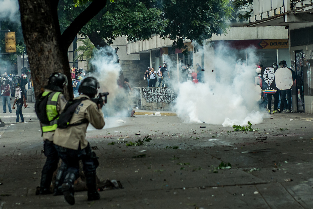 CARACAS, VENEZUELA - MAY 8, 2017: National police fire tear gas canisters at anti-government protesters. The streets of Caracas and other cities across Venezuela have been filled with tens of thousands of demonstrators for nearly 100 days of massive protests, held since April 1st. Protesters are enraged at the government for becoming an increasingly repressive, authoritarian regime that has delayed elections, used armed government loyalist to threaten dissidents, called for the Constitution to be re-written to favor them, jailed and tortured protesters and members of the political opposition, and whose corruption and failed economic policy has caused the current economic crisis that has led to widespread food and medicine shortages across the country.  Independent local media report nearly 100 people have been killed during protests and protest-related riots and looting.  The government currently only officially reports 75 deaths.  Over 2,000 people have been injured, and over 3,000 protesters have been detained by authorities.  PHOTO: Meridith Kohut