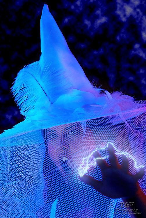 Young screaming woman with a witches' hat shoots electricity from her fingertips.Black light