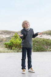 little boy with his hands open to the sky