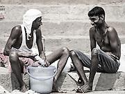 Zwei Wasch-Männer am Ganges. Unser Guide hat uns erklärt, dass sie gerne das Handwerk ihrer Vorfahren fortführen. Ein langjähriger Kundenstamm erlaubt ihnen, ein bestehendes Geschäft fortzuführen. Etwas anderes zu machen wäre für sie schwieriger. Sie sind auch stolz auf ihr Geschäft. Ihre Frauen trocknen die Wäsche.