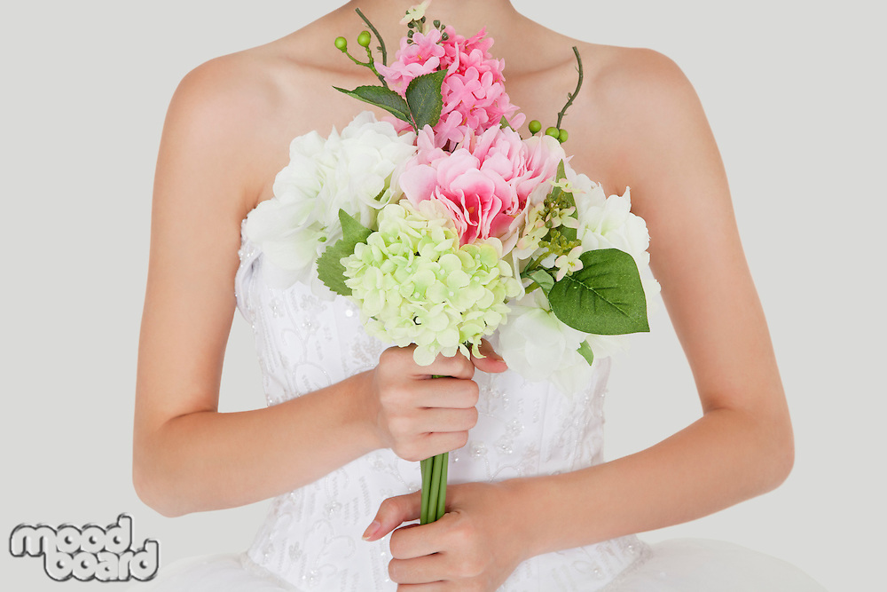 Midsection of young bride holding fresh bouquet