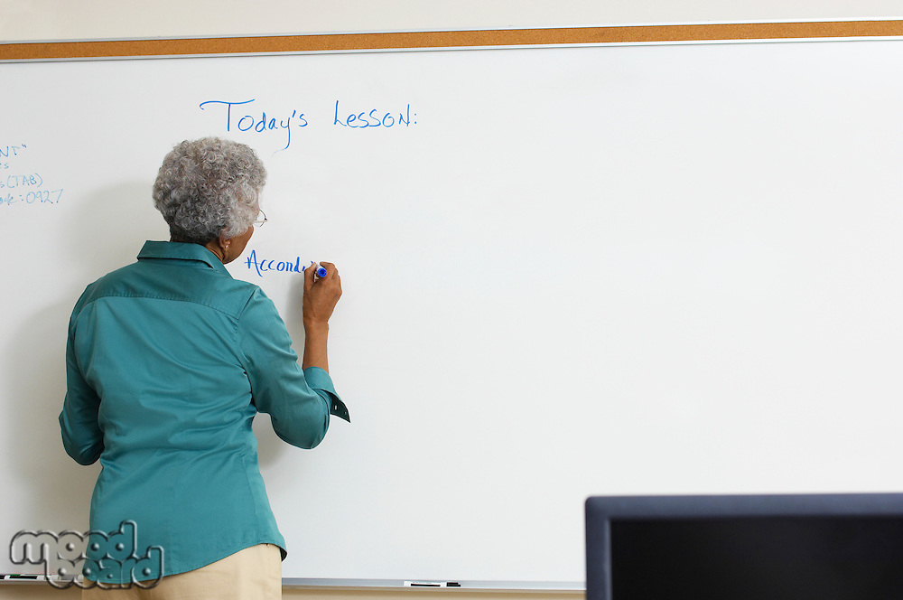 Female teacher writing on whiteboard in classroom