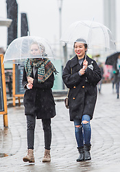 © Licensed to London News Pictures. 30/03/2018. Brighton, UK. Members of the public shelter from the rain as they visit Brighton and Hove on Good Friday with wet weather expected to last for the whole Easter Bank Holliday weekend. Photo credit: Hugo Michiels/LNP