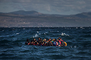 Afghan migrants on an overcrowded inflatable boat approach the Greek island of Lesbos in bad weather after crossing the Aegean see from Turkey, Wednesday, Oct. 28, 2015. Greece's government says it is preparing a rent-assistance program to cope with a growing number of refugees, who face the oncoming winter and mounting resistance in Europe. (AP Photo/Santi Palacios)