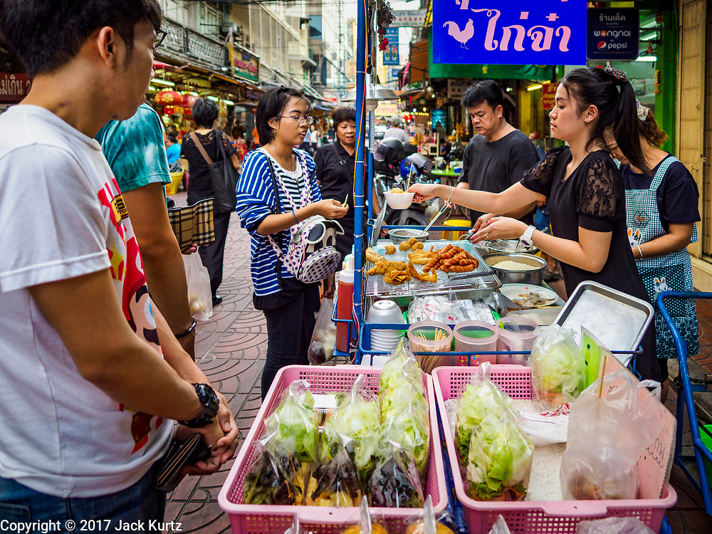"""18 MAY 2017 - BANGKOK, THAILAND: A fried meat street stall on a side street in Bangkok's Chinatown. City officials in Bangkok have taken steps to rein in street food vendors. The steps were originally reported as a """"ban"""" on street food, but after an uproar in local and international news outlets, city officials said street food vendors wouldn't be banned but would be regulated, undergo health inspections and be restricted to certain hours on major streets. On Yaowarat Road, in the heart of Bangkok's touristy Chinatown, the city has closed some traffic lanes to facilitate the vendors. But in other parts of the city, the vendors have been moved off of major streets and sidewalks.      PHOTO BY JACK KURTZ"""