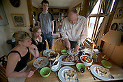 ICE.MWdrv04.64.xf1brw..Björn Thoroddsen carves lamb as his wife Margret (Linda) Gunnlaugsdottir and two of their children (Gestur Björnsson, 21; Thordis Björnsdottir) look on in Hafnarfjördur, Iceland, outside Reykjavik. Ten years ago he and his family were the Icelandic participants in Material World: A Global Family Portrait, 1994 for which they took all of their possessions out of their house for a family and possessions portrait in the snow. Pages 162-163. {{Central image from original book project is: ICE.mw.01.xxs.}}.