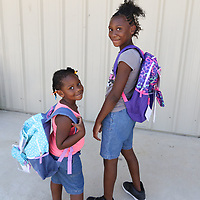LIBBY EZELL | BUY AT PHOTOS.DJOURNAL.COM<br /> Karlee, 3 left, and Kaniya, 9, Gillespie proudly show off their new backpacks full of school supplies provided by Officer Jermandy R. Jackson Saturday at Verona City Park
