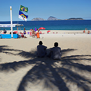Locals sit in the shade of a palm tree on Ipanema Beach, Rio de Janeiro, Brazil. 6th July 2010. Photo Tim Clayton..The beaches of Rio de Janeiro, provide the ultimate playground for locals and tourists alike. Beach activity is in abundance as beach volley ball, football and a hybrid of the two, foot volley, are played day and night along the length and breadth of Rio's beaches. .Volleyball nets and football posts stretch along the cities coastline and are a hive of activity particularly at it's most famous beaches Copacabana and Ipanema. .The warm waters of the Atlantic Ocean provide the ideal conditions for a variety of water sports. Walkways along the edge of the beaches along with exercise stations and cycleways encourage sporting activity, even an outdoor gym is available at the Parque Do Arpoador overlooking the ocean. .On Sunday's the main roads along the beaches of Copacabana, Leblon and Ipanema are closed to traffic bringing out thousands of people of all ages to walk, run, jog, ride, skateboard and cycle more than 10 km of beachside roadway. .This sports mad city is about to become a worldwide sporting focus as they play host to the world's biggest sporting events with Brazil hosting the next Fifa World Cup in 2014 and Rio de Janeiro hosting the Olympic Games in 2016..