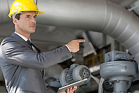 Confident young male manager with digital tablet pointing at machinery in industry