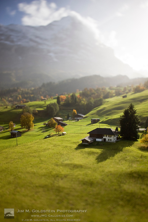 An aerial view of homes on the hillsides of Grindelwald, Switzerland with the Eiger peak in the background