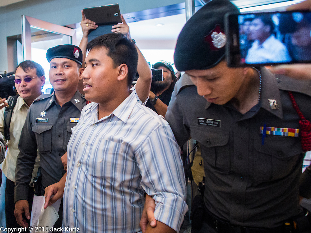 "14 FEBRUARY 2015 - BANGKOK, THAILAND: Thai police lead away Student activist Siriwit Serithiwat after they arrested him during a protest the military coup. Martial law is still in effect in Thailand and protests against the coup are illegal. Dozens of people gathered in front of the Bangkok Art and Culture Centre in Bangkok Saturday to hand out red roses and copies of George Orwell's ""1984."" Protestors said they didn't support either Red Shirts or Yellow Shirts but wanted a return of democracy in Thailand. The protest was the largest protest since June 2014, against the military government of General Prayuth Chan-Ocha, who staged the coup against the elected government. Police made several arrests Saturday afternoon but the protest was not violent.      PHOTO BY JACK KURTZ"