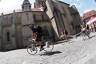 Picture by Andrew Tobin/Tobinators Ltd +44 7710 761829<br /> 04/08/2013<br /> Riders go past the cathedral during the Cycle Messenger World Championships held in Lausanne, Switzerland. Started in 1993 by Achim Beier from Berlin, the championships are not only a sporting contest but an opportunity to unite friends and bicycle enthusiasts worldwide. The event comprises a number of challenges including a sprint, a track stand (longest time stationary on the bike), a cargo race where heavy loads are carried on special bikes, and the main race. The course winds through central Lausanne and includes bridges, stairs, cobbles, narrow alleyways and challenging hills. The main race simulates the job of a bike courier making numerous drops and pickups across the city. Riders need to check in at specific checkpoints, hand over their delivery and get a new one. The main race can take up to 4 hours for each competitor to complete.