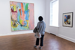 """© Licensed to London News Pictures. 02/10/2018. LONDON, UK. A visitor views (L) """"Die Dornenkrönung (The Crowning with Thorns)"""", 1983, by Georg Baselitz.  Preview of """"A Focus on the 1980s"""", an exhibition of works by Georg Baselitz at Galerie Thaddaeus Ropac in Mayfair.  The show features seminal paintings, previously unseen works, drawings and early sculptures by the artist during his breakthrough decade and runs 3 October to 21 November 2018.  Photo credit: Stephen Chung/LNP"""