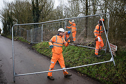 Harefield, UK. 14 January, 2020. Men wearing HS2 overalls erect fencing around woodland close to a protection camp from which Stop HS2 activists are being evicted. Part of the nearby Colne Valley protection camp was evicted by bailiffs last week. 108 ancient woodlands are set to be destroyed by the high-speed rail link and further destruction of trees for HS2 in the Harvil Road area is believed to be imminent.
