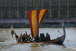 Viking warrior-crew boat on the River Thames photocall. A replica of a Viking boat sails on the River Thames opposite the Houses of Parliament with a Crew of Vikings for the forthcoming live broadcast in cinemas across the UK of Vikings Live from the British Museum . Westminster Bridge, London, United Kingdom. Tuesday, 15th April 2014. Picture by Daniel Leal-Olivas / i-Images