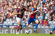 Uche Ikpeazu (#19) of Heart of Midlothian FC runs at Shaun Rooney (#2) of Inverness Caledonian Thistle FC during the William Hill Scottish Cup semi-final match between Heart of Midlothian and Inverness CT at Hampden Park, Glasgow, United Kingdom on 13 April 2019.