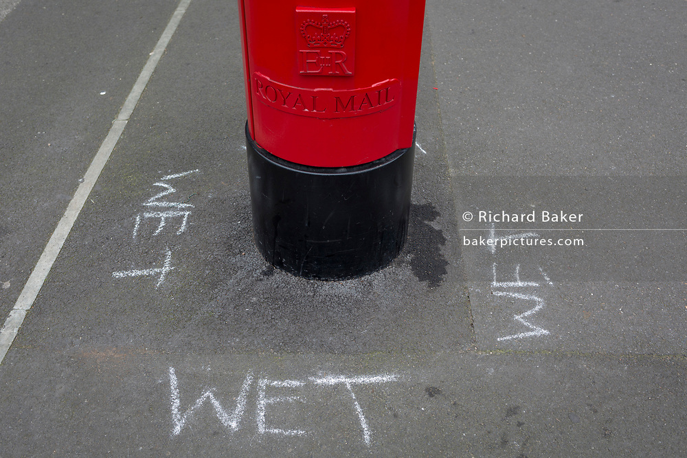 Chalk writing warns letter posters of a freshly-painted Royal Mail postal box in Dulwich Village, on 7th January 2019, in Southwark, London, UK.