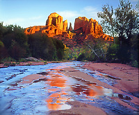 I waited for the sandstone rocks to glow before setting up my camera at a low angle to shoot Cathedral Rock reflecting in Oak Creek at sunset and getting this photo.
