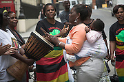 Rally in central London held by MDC every Saturday to protest against Robert Mugabe and his regime in Zimbabwe.Women drumming and dancing with baby in back carrier sling.
