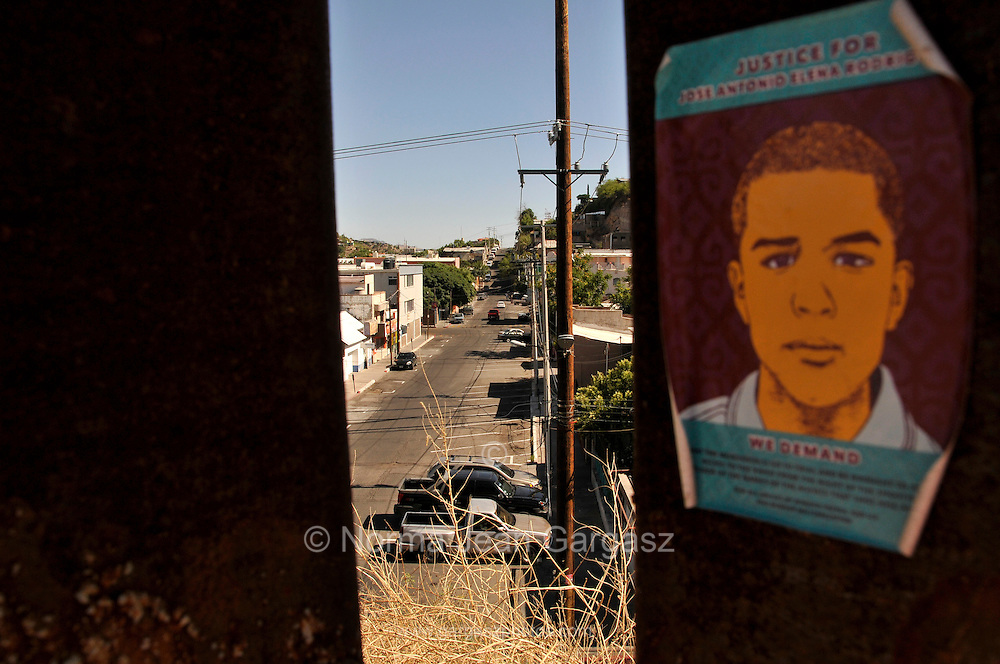 Posters placed on the U.S. side of the border wall call for justice for Mexican teenager, Jose Antonio Elena Rodriguez, 16, who was allegedly shot and killed by U.S. Border Patrol agents firing through the fence in to Nogales, Sonora, where the youth was reported by a witness to be walking down Calle Internacional on October 10, 2012.  The agents claim the the youth was throwing rocks at them either through or over the border fence in to Nogales, Arizona, USA.  A cross memorializes the youth at the location in Mexico where he died.
