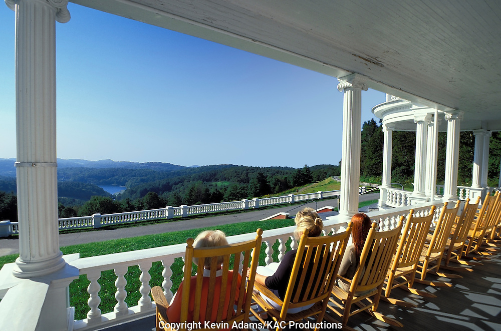 Visitors enjoy the view from the front porch of the Manor House at Moses Cone Memorial Park on the Blue Ridge Parkway in North Carolina. The house was featured in the movie The Green Mile, starring Tom Hanks. Bass Lake is in the distance.