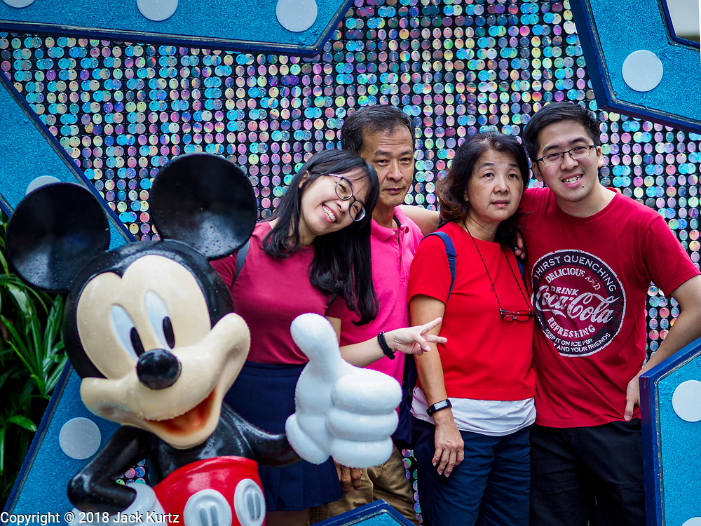 "12 DECEMBER 2018 - SINGAPORE: A family poses for a photo with Mickey Mouse at a Christmas display on Orchard Road. Orchard Road is the main shopping district of Singapore and for years hosts a large light display around Christmas. The main sponsor of this year's display is the Disney Company and the displays are decorated with characters from the Disney entertainment universe. This has upset some religious leaders in Singapore and the National Council of Churches of Singapore (NCCS) sent a letter to the Singapore Tourism Board (STB) expressing its concern about the ""increasing secularisation and commercialization of Christmas"" in Singapore. The STB reached out to the NCCS, but the Orchard Road lights will remain on through the holidays.   PHOTO BY JACK KURTZ"