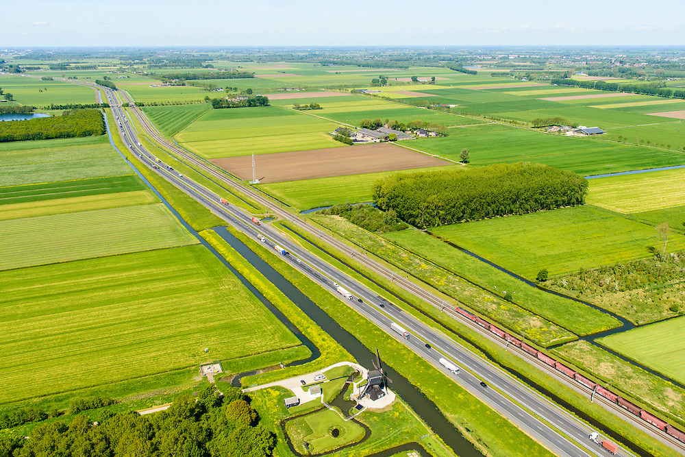 Nederland, Gelderland, Gemeente Zaltbommel, 23-08-2016; Rijksweg A15 ten westen van knooppunt Deil . Parallel aan de snelweg de Betuweroute met goederentrein (kolen en/of erts), richting haven van Rotterdam. Onder in beeld de Laaglandse molen aan de Haaftensche Molenvliet.<br /> Main motorway A15 (Rotterdam Harbour - Germany) with Betuweroute, freight railway w coal train <br /> <br /> aerial photo (additional fee required); luchtfoto (toeslag op standard tarieven); copyright foto/photo Siebe Swart