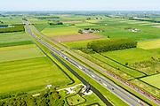 Nederland, Gelderland, Gemeente Zaltbommel, 23-08-2016; Rijksweg A15 ten westen van knooppunt Deil . Parallel aan de snelweg de Betuweroute met goederentrein (kolen en/of erts), richting haven van Rotterdam. Onder in beeld de Laaglandse molen aan de Haaftensche Molenvliet.<br /> Main motorway A15 (Rotterdam Harbour - Germany) with Betuweroute, freight railway w coal train <br /> <br /> aerial photo (additional fee required); luchtfoto (toeslag op standard tarieven); copyright foto/photo Siebe Swart