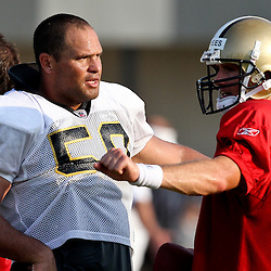 August 6, 2011; Metairie, LA, USA; New Orleans Saints quarterback Drew Brees (9) talks with center Olin Kreutz (50) during training camp practice at the New Orleans Saints practice facility. Mandatory Credit: Derick E. Hingle
