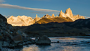 "A golden sunrise spotlights Mount Fitz Roy (3405 meters or 11,170 feet), which rises abruptly on the border between Argentina and Chile in the Southern Patagonian Ice Field in the Andes mountains, near El Chaltén village, in Los Glaciares National Park, Argentina, South America. In 1877, explorer Perito Moreno named ""Cerro Fitz Roy"" for Robert FitzRoy (no space before the capital R) who, as captain of the HMS Beagle, had travelled up the Santa Cruz River in 1834 and charted much of the Patagonian coast. First climbed in 1952 by French alpinists Lionel Terray and Guido Magnone, Mount Fitz Roy has very fickle weather and is one of the world's most challenging technical ascents. It is also called Cerro Chaltén, Cerro Fitz Roy, and Monte Fitz Roy (all with a space before the R). Chaltén comes from a Tehuelche (Aonikenk) word meaning ""smoking mountain"" (explained by frequent orographic clouds). Cerro is a Spanish word meaning hill. El Chaltén village was built in 1985 by Argentina to help secure the disputed border with Chile, and now tourism supports it, 220 km north of the larger town of El Calafate. The foot of South America is known as Patagonia, a name derived from coastal giants, Patagão or Patagoni, who were reported by Magellan's 1520s voyage circumnavigating the world and were actually Tehuelche native people who averaged 25 cm (or 10 inches) taller than the Spaniards. Mount Fitz Roy is the basis for the Patagonia company's clothing logo, after Yvon Chouinard's ascent and subsequent film in 1968. Panorama stitched from 2 overlapping photos."