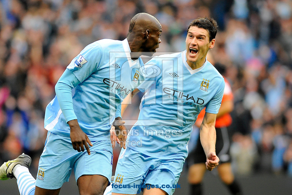 Picture by Ste Jones/Focus Images Ltd.  07706 592282.24/9/11.Mario Balotelli and Gareth Barry of Manchester City of Manchester City celebrates the opening goal during the Barclays Premier League match at Etihad Stadium, Manchester.