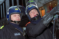 Two police officers in riot gear patrolling in central London during Mayday demonstrations.