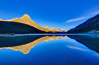 Alpenglow on the mountain peaks surrounding Lower Waterfowl Lake at Sunrise with the mountains reflected the glassy calm waters of the lake.<br /> <br /> &copy;2015, Sean Phillips<br /> http://www.RiverwoodPhotography.com
