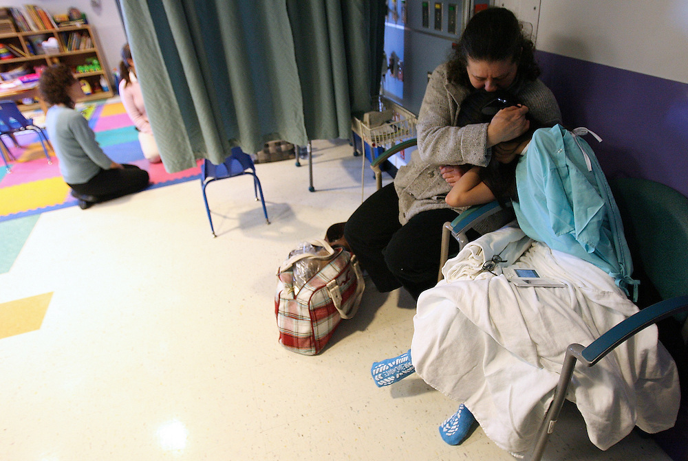 "2/13/2009 Baltimore, MD-  Lani Dickinson, 14, is comforted by her mother Julie Bell in a waiting room at Johns Hopkins Hospital before she undergoes surgery for the ""revision of her transhumeral amputation.""  Lani was born in China with a congenital defect and adopted by an American family.  Despite her disability, she trains hard as a ballerina and would like to someday be a professional dancer.  Photo by Lisa Hornak"