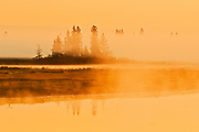 Fog rising above Whirlpool Lake at sunrise<br /> Riding Mountain National Park<br /> Manitoba<br /> Canada
