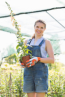Portrait of happy gardener holding potted plants at greenhouse