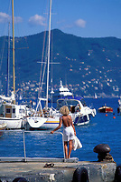 woman standing on port looking at the boats in Portofino, Liguria, Italy